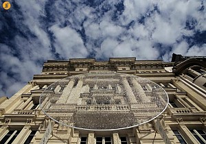 خلاقیت در استفاده از شیشه های عینک برای خلق تندیسی بر روی نمای ساختمانی کلاسیک